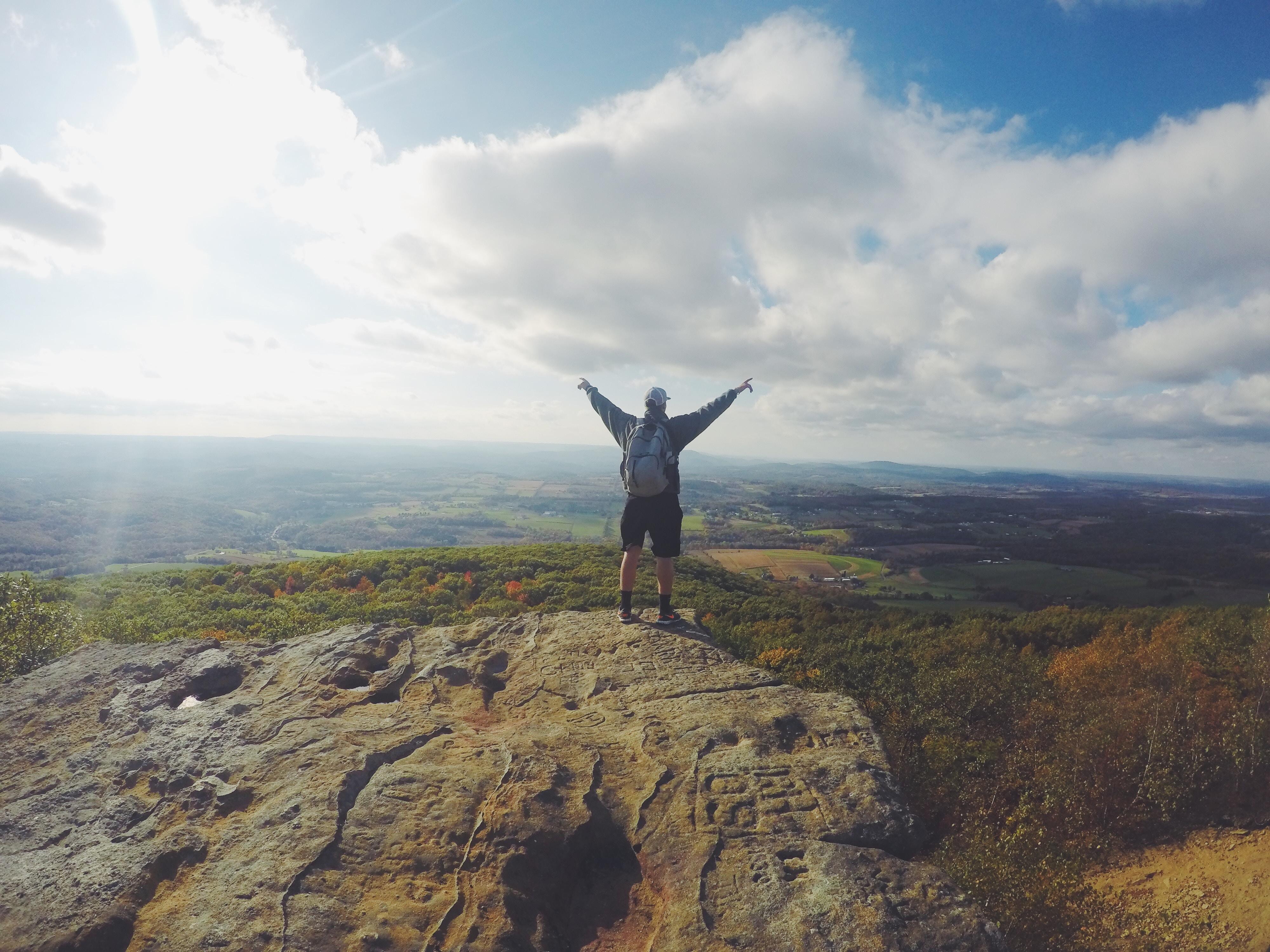 personne au bord d'une falaise les mains en l'air